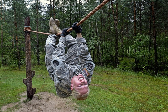 Spc. Elizabeth Ibabao goes across a rope bridge at the obstacle course during U.S. Army Europe's Best Warrior competition in Grafenwoehr, Germany, Aug. 20, 2013. The week-long event tests a Soldier's physical stamina, leadership, technical knowledge and skill.