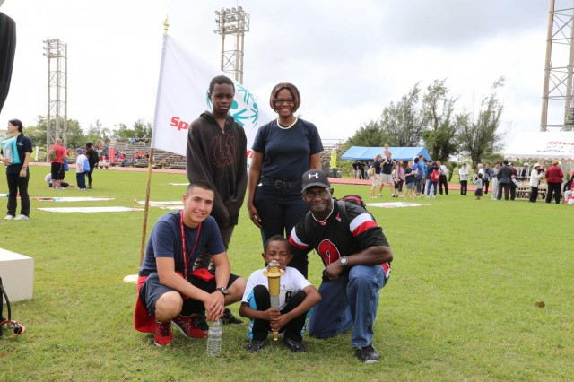"Immediately after the opening ceremony for Special Olympics on Kadena Air Base Nov. 2, U.S. Army Staff Sgt. Tony Williams, an operations noncommissioned officer, 10th Regional Support Group, gathered with his family adjacent to the ""Flame of Hope"" at the Risner Sporting Complex. From left to right, Williams oldest son, Terrell, his wife Jacqueline, and his youngest son holding the torch, Jermaine, kneeling next to Jermaine was Iglesias who volunteered throughout the day to assist Jermaine during the competition."