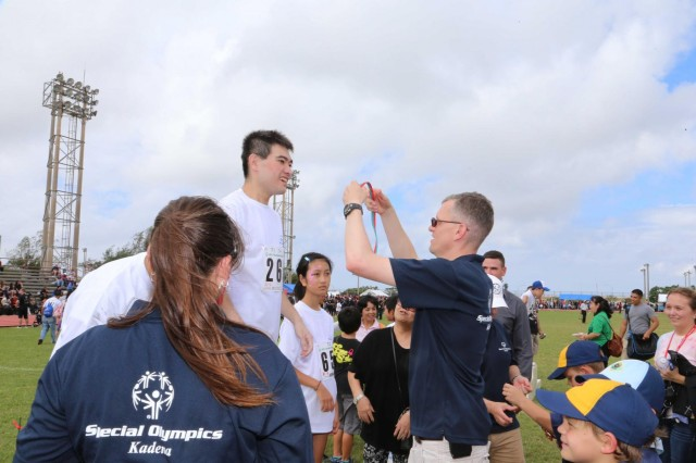 Lt. Col. Benjamin Ogden, commander, 1st Battalion, 1st Air Defense Artillery, presents medals immediately following the 100 meter competition at the 14th Annual Special Olympics Games on Kadena Air Base, Nov. 2. Approximately 100 U.S. soldiers volunteered to assist and cheer on the athletes during the games.  From Special Olympics beginning on Okinawa in 2000, the goals remain unchanged: to not only promote the understanding and acceptance of people with intellectual and physical disabilities, but to foster stronger bonds and friendships between the U.S. and Japan.