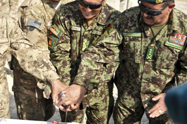 FORWARD OPERATING BASE AZIZULLAH, Afghanistan -- U.S. Army Lt. Col. Eric Smith (left), commander of 3rd Squadron, Combined Task Force Dragoon, Afghanistan National Army Lt. Col. Babakhan Hassani (middle), commander of 4th Kandak and Col. Said Zainuddin Rohani (right), commander of 6th Kandak, both with 3rd Brigade, 205th Corps, cut a cake together after a transfer ceremony Nov. 15, 2013, at Forward Operating Base Azizullah, Afghanistan. Troops with 3rd Squadron relinquished authority over the base to the ANA and Afghan National Civil Order Police in support of Operation Enduring Freedom.