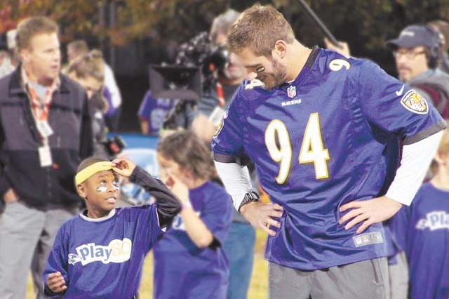 (From right) Baltimore Ravens offensive linebacker John Simon chats with 7-year-old Ja` Zae Jones during the NFL Play 60 youth combine at Aberdeen Proving Ground hosted by DFMWR and CYSS Nov. 6.