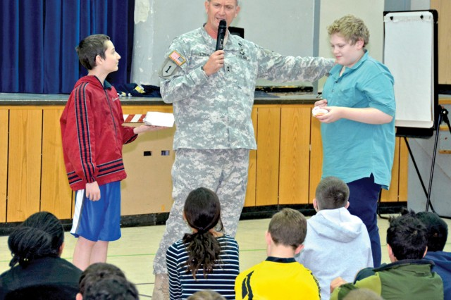 Maj. Gen. Richard C. Longo, U.S. Army Europe deputy commander, is joined by Wiesbaden Middle School seventh-grader Matthew Cox (left) and eighth-grader Oishin Oravetz while taking a poll among students about different food choices.