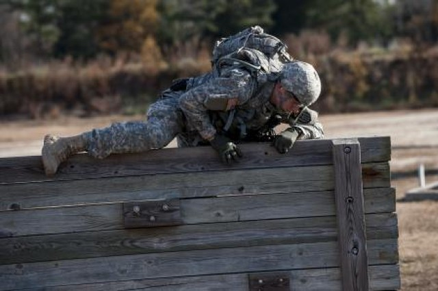 Spc. Mitchell Fromm, with the 428th Engineer Company, of Stevens Point, Wis., navigates across an obstacle course during the first day of the Best Warrior Competition at Fort Lee, Va., Nov. 20, 2013.