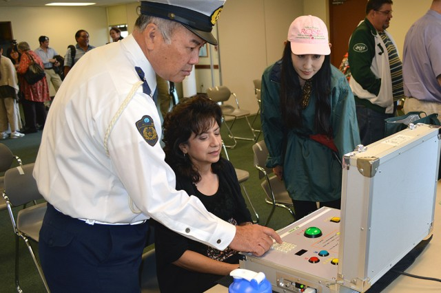 In this simulation hosted by emergency services personnel, participants must properly use a fire extinguishers to put out the fire during a Safety Day event on Torii Station on Nov. 21, 2013.