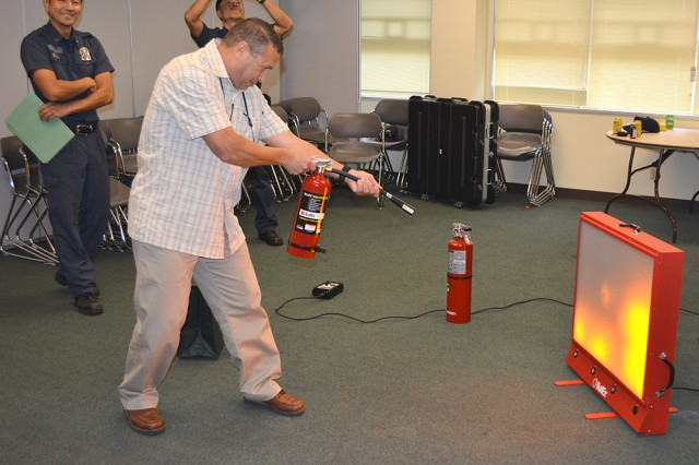 In this simulation hosted by emergency services personnel, participants must properly use a fire extinguisher to put out the fire during a Safety Day event on Torii Station on Nov. 21, 2013.