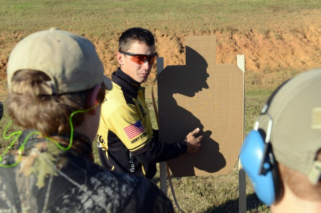 Staff Sgt. Daniel Horner, U.S. Army Marksmanship Unit, explains shots on a target, Oct. 26, 2013, during the 6th annual USAMU Action Shooting Junior Clinic at Krilling Range on Fort Benning, Ga. More than 30 junior shooters from across the country came to Fort Benning to enhance their marksmanship skills from members of the USAMU's Action Shooting team.