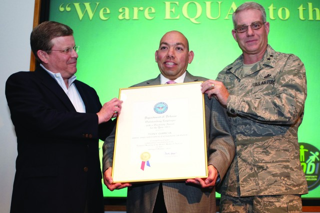 Fort Knox PX custodial worker Tony Garcia receives the Dept of Defense 2013 Worldwide Outstanding Employee with a Disability Award Saturday at AAFES Headquarters in Dallas from AAFES CEO Tony Shull (left) and Deputy AAFES Director, Air Force MG Ward. Garcia is the son of USAREC deputy G3 director Todd Sherman and his wife Gloria.