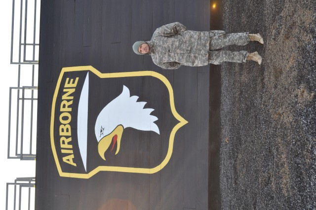 """Capt. Jason Burnes, an assistant operations officer at Headquarters and Headquarters Company, 3rd Special Troops Battalion, 3rd Brigade Combat Team """"Rakkasan"""", 101st Airborne Division stands in front of one of the repelling towers shortly after completing the culminating 12 mile foot march for Air Assault School on Nov. 22, 2013.  Burnes set a new record time of one hour and 37 minutes during the event."""