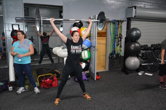 CAMP CASEY, South Korea - Christa Castillo (right), the wife of Sgt. 1st Class Alberto Castillo, an infantry platoon sergeant assigned to 2nd Battalion, 9th Infantry Regiment, 1st Armored Brigade Combat Team, 2nd Infantry Division, both from Winnsboro, Texas, demonstrates how to properly perform a power clean hang snatch Nov. 13, 2013 at Carey Fitness Center on Camp Casey, South Korea. (U.S. Army photo by Staff Sgt. Carlos R. Davis, 210th Fires Brigade Public Affairs/Released).