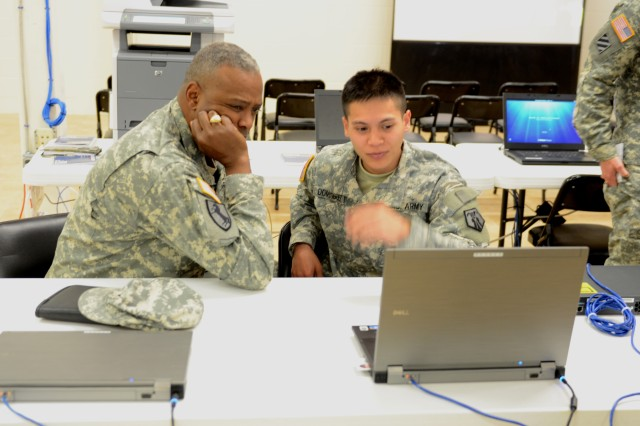 U.S. Army Spc. Nicholas Dominguez, assigned to 406th Human Resources Company, Kaiserslautern, Germany, shows Brig. Gen. Barrye L. Price, G1 Deputy Chief of Staff, Forces Command, Fort Bragg, N.C., different update briefs on his computer he gives to inbound and outbound personnel processing through the Gateway during Silver Scimitar at Fort Devens, Mass., Nov. 15, 2013. Silver Scimitar is the U.S. Army Forces Command's bi-annual, multi-echelon training exercise designed to train Human Resources units scheduled for deployment on core competencies for operations within a deployed area of responsibility. (U.S. Army photo by Sgt. Dianne M. Carter/Released)