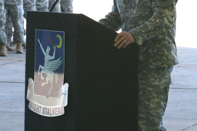 Following Army tradition, from left, Col. John Evans, regiment commander, 160th Special Operations Aviation Regiment, or SOAR, (A), passes the company guidon to Maj. David Rousseau, company commander, during the Company E, 160th SOAR (A) activation ceremony, Tuesday, at Libby Army Airfield.