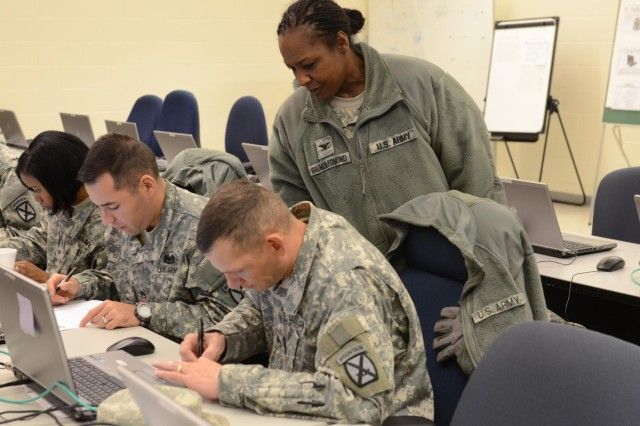 U.S.  Army Col. Elvia Denise Gaines-Edmond, Human Resources Training Assessment branch chief and Silver Scimitar exercise director, looks on as U.S. Army Staff Sgt. Albert Daroca and Staff Sgt. Adan Parra, both assigned to 10th Mountain Division, Fort Drum, N.Y., check documents for mistakes during the Silver Scimitar exercise at Fort Devens, Mass., Nov. 14, 2013. Silver Scimitar is the U.S. Army Forces Command's bi-annual, multi-echelon training exercise designed to train Human Resources units scheduled for deployment on core competencies for operations within a deployed area of responsibility. (U.S. Army photo by Sgt. Dianne M. Carter/Released)
