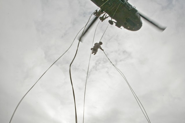 U.S. Army Sgt. 1st Class Jeremy Jackson, a course chief at the Fort Hood Air Assault School who is from New Orleans, stabilizes a rope from the ground as four of his instructors rappel out of a UH-60 Black Hawk hovering 85 feet above the ground as a demonstration for students of class 02-14, Nov. 20, 2013. Air Assault School is a grueling 10-day course that qualifies soldiers to conduct airmobile and air assault helicopter operations, to include aircraft orientation, sling load operations, proper rappelling techniques and fast-rope techniques. The high standards of the school require the student to take part in a 12-mile march with rucksack in under three hours on the morning of graduation to be awarded their wings. Every iteration of the Fort Hood Air Assault School begins with 132 students, and ends with an average of 80 graduates. On the day this photo was taken, class 02-14 was down to 46 students.  (U.S. Army photo by Sgt. Ken Scar, 7th Mobile Public Affairs Detachment)