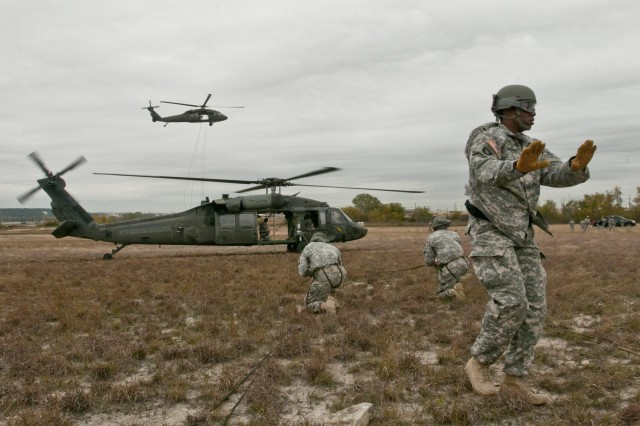 U.S. Army Sgt. Anthony Eashman, of San Francisco, Cali., instructs students of the Fort Hood Air Assault School class 02-14 during phase three rappel testing, Nov. 20, 2013. Air Assault School is a grueling 10-day course that qualifies soldiers to conduct airmobile and air assault helicopter operations, to include aircraft orientation, sling load operations, proper rappelling techniques and fast-rope techniques. The high standards of the school require the student to take part in a 12-mile march with rucksack in under three hours on the morning of graduation to be awarded their wings. Every iteration of the Fort Hood Air Assault School begins with 132 students, and ends with an average of 80 graduates. On the day this photo was taken, class 02-14 was down to 46 students.  (U.S. Army photo by Sgt. Ken Scar, 7th Mobile Public Affairs Detachment)