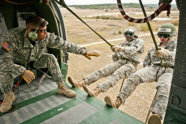 U.S. Army Sgt. 1st Class Jeremy Stanton of Midland, Texas, instructs two students of Fort Hood Air Assault School class 02-14 as they prepare to rappel 85 feet out of a UH-60 Black Hawk during phase three testing, Nov. 20, 2013. Air Assault School is a grueling 10-day course that qualifies soldiers to conduct airmobile and air assault helicopter operations, to include aircraft orientation, sling load operations, proper rappelling techniques and fast-rope techniques. The high standards of the school require the student to take part in a 12-mile march with rucksack in under three hours on the morning of graduation to be awarded their wings. Every iteration of the Fort Hood Air Assault School begins with 132 students, and ends with an average of 80 graduates. On the day this photo was taken, class 02-14 was down to 46 students.  (U.S. Army photo by Sgt. Ken Scar, 7th Mobile Public Affairs Detachment)