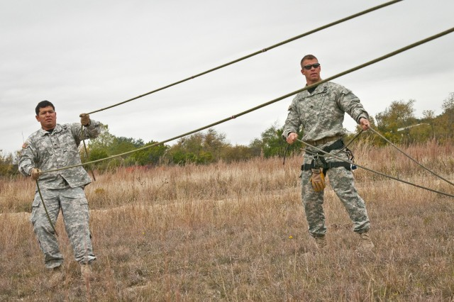 Fort Hood Air Assault instructors Sgt. Jon Garcia (left), from Santa Cruz, Cali., and Sgt. 1st Class Jeremy Stanton, from Midland, Texas, untangle ropes before conducting phase three rappel testing, Nov. 20, 2013. Air Assault School qualifies soldiers to conduct airmobile and air assault helicopter operations, to include aircraft orientation, sling load operations, proper rappelling techniques and fast-rope techniques. The school itself is 10 days of rigorous, fast paced training. The high standards of the school require the student to take part in a 12-mile march with rucksack in under three hours on the morning of graduation to be awarded their wings. Every iteration of the Fort Hood Air Assault School begins with 132 students, and ends with an average of 80 graduates. (U.S. Army photo by Sgt. Ken Scar, 7th Mobile Public Affairs Detachment)