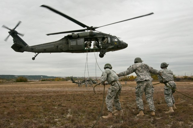 Fort Hood Air Assault instructor Sgt. Anthony Eashman (center), from San Francisco, Cali., guides two students during phase three rappel testing, Nov. 20, 2013. Air Assault School qualifies soldiers to conduct airmobile and air assault helicopter operations, to include aircraft orientation, sling load operations, proper rappelling techniques and fast-rope techniques. The school itself is 10 days of rigorous, fast paced training. The high standards of the school require the student to take part in a 12-mile march with rucksack in under three hours on the morning of graduation to be awarded their wings. Every iteration of the Fort Hood Air Assault School begins with 132 students, and ends with an average of 80 graduates. (U.S. Army photo by Sgt. Ken Scar, 7th Mobile Public Affairs Detachment)