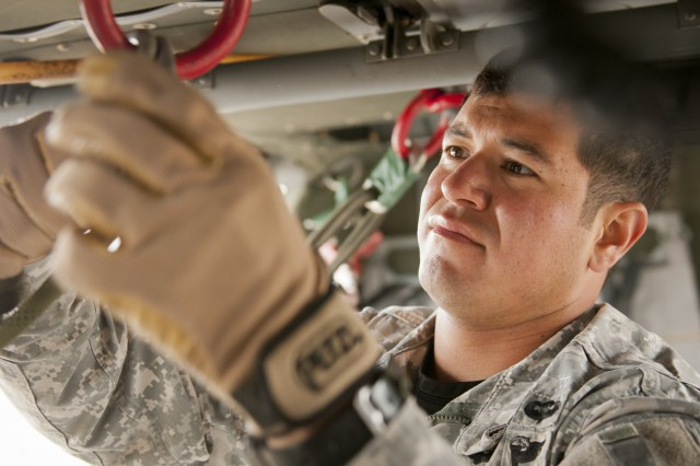 Fort Hood Air Assault instructor Sgt. Jon Garcia, from Santa Cruz, Cali., inspects the safety equipment of a UH-60 Black Hawk during phase three rappel testing of class 02-14, Nov. 20, 2013. Air Assault School qualifies soldiers to conduct airmobile and air assault helicopter operations, to include aircraft orientation, sling load operations, proper rappelling techniques and fast-rope techniques. The school itself is 10 days of rigorous, fast paced training. The high standards of the school require the student to take part in a 12-mile march with rucksack in under three hours on the morning of graduation to be awarded their wings. Every iteration of the Fort Hood Air Assault School begins with 132 students, and ends with an average of 80 graduates. (U.S. Army photo by Sgt. Ken Scar, 7th Mobile Public Affairs Detachment)