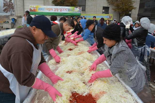 "Soldiers from 210th Fires Brigade, 2nd Infantry Division, and citizens of Dongducheon work side-by-side to make kimchi at the Annual Kimchi Charity Event, Nov. 15, 2013, in Dongducheon, South Korea. It's a way for Soldiers to experience a ""Thanksgiving"" meal from a different culture."