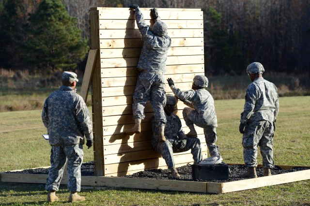 Sgt. 1st Class Ronnie Reynolds (center) helps Soldiers scale a wall, as he leads a team in moving personnel and a 40-pound ammunition box over the obstacle, at the Best Warrior Competition at Fort Lee, Va., Nov. 21, 2013.