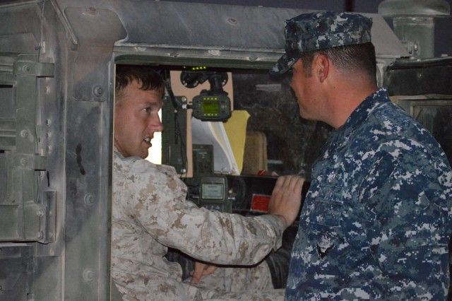 Marine Staff Sgt. Christopher Harrison, lightweight armored vehicle crewman, and Navy Petty Officer 2nd Class Garrett Brunson, an information systems technician, boot up the vehicle-mounted, Joint Battle Command Platform prior to a convoy at McGregor Range Complex, N.M., Nov. 13, 2013.  The service members are participating in Network Evaluation Integration 14.1, a semi-annual evaluation and testing of new equipment and systems with a focus on modernization. Marine Corps Systems Command coordinated the Marine Corps portion of the testing. (Photo by Staff Sgt. Candice Harrison, 24th Press Camp Headquarters, Fort Bliss, Texas)