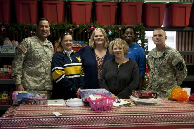 Lt. Col. Michael Trotter (left), commander of the 2nd Battalion, 1st Infantry Regiment, 2-2 Stryker Brigade Combat Team, 7th Infantry Division, and Command Sgt. Maj. John Roome (right), command sergeant major of 2-1 Infantry, pose for a photo with the Lisa Bennett (center), president of Santa's Castle, and three Santa's Castle volunteers, Nov. 18. Santa's Castle is a Joint Base Lewis-McChord, Wash., based nonprofit organization that raises toys to help struggling military families and their children have a memorable Christmas. (Photo by Staff Sgt. Bryan Dominique, 2-2 Stryker Brigade Combat Team, 7th Infantry Division)