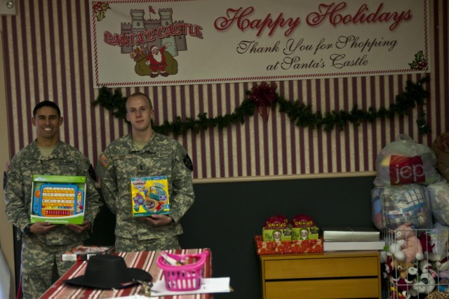 Sgt. Miguel, Romero (left), a Dexter, N.M., native assigned to Company C, 2nd Battalion, 1st Infantry Regiment, 2-2 Stryker Brigade Combat Team, 7th Infantry Division, and 1st Lt. Brian Rook, the 2-1 Infantry chemical officer, hold two of the more than 100 toys raised during their battalion toy drive, Nov. 18 at Santa's Castle on Joint Base Lewis-McChord, Wash. Santa's Castle is a nonprofit organization that raises toys to help struggling military families and their children have a memorable Christmas. (Photo by Staff Sgt. Bryan Dominique, 2-2 Stryker Brigade Combat Team, 7th Infantry Division)