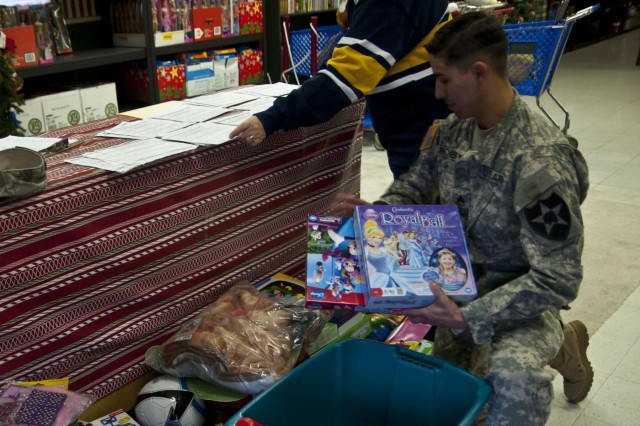 Sgt. Miguel Romero, a Dexter, N.M., native assigned to Company C, 2nd Battalion, 1st Infantry Regiment, 2-2 Stryker Brigade Combat, 7th Infantry Division, delivers toys raised during the 2-1 Infantry toy drive to Santa's Castle, Nov. 18. Santa's Castle is a Joint Base Lewis-McChord, Wash., based nonprofit organization that raises toys to help struggling military families and their children have a memorable Christmas. (Photo by Staff Sgt. Bryan Dominique, 2-2 Stryker Brigade Combat Team, 7th Infantry Division)