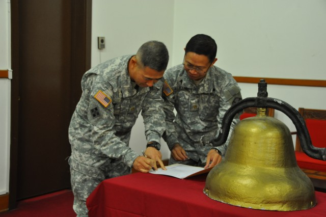 Chaplain Maj. Alwyn. S. Albano, former director of the Religious Retreat Center, signs a document stating the transfer of RRC bell during the decommissioning ceremony of RRC, Nov. 21. The functions and community services of the RRC have relocated to the South Post Chapel on U.S. Army Garrison Yongsan, to continue serving the community members as it has for the past 58 years. The land previously occupying the RRC is being returned to the Korean government as part of the Area II transformation plan. (U.S. Army photo by Cpl. Jung Jihoon)
