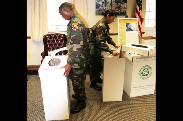 (From Left) Mark Pollard and Vanessa Marroquin from the Freestate ChalleNGe Academy assemble recycling receptacles bearing the installation's new Recycling Program slogan and logo in the Garrison Headquarters Bldg. 305 Nov. 15 in conjunction with  the Directorate of Public Works environmental division's America Recycles Day observance.