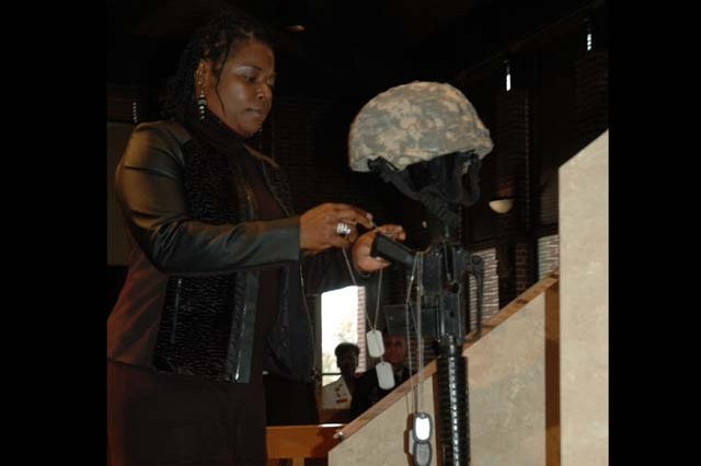Tonya Armstead places an ID tag on the Maryland Fallen Soldiers memorial in honor of her husband Sgt. 1st Class Moses Armstead, during the Veterans Day and Survivor Outreach Services event honoring veterans and Survivors at the APG