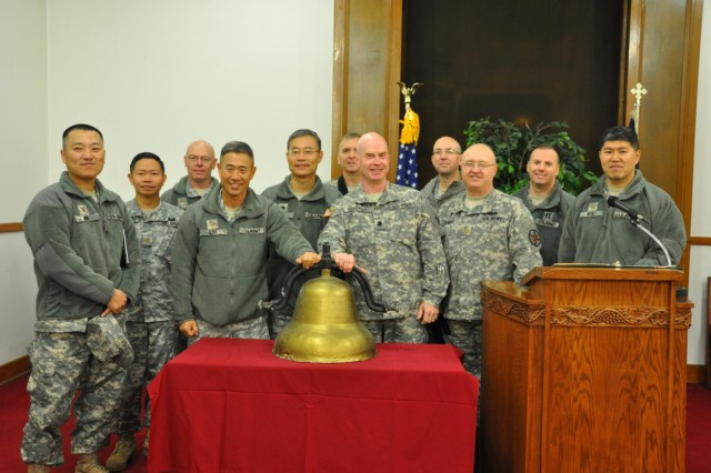 The U.S. Army chaplains of Area II pose with the Religious Retreat Center bell, a symbol of the RRC, during the decommissioning ceremony, Nov. 21. The functions and community services of the RRC have relocated to the South Post Chapel on U.S. Army Garrison Yongsan, to continue serving the community members as it has for the past 58 years. The land previously occupying the RRC is being returned to the Korean government as part of the Area II transformation plan. (U.S. Army photo by Cpl. Jung Jihoon)