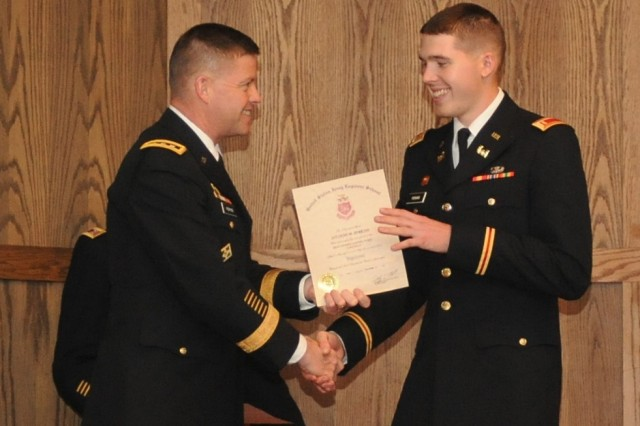 Lt. Gen. David Perkins, Combined Arms Center and Fort Leavenworth commanding general, congratulates his son, 2nd Lt. Chad Perkins, and presents him with his certificate during the Engineer Basic Officer Leadership Course Class 10-13 graduation held in the Engineer Regimental Room in the John B. Mahaffey Museum on Fort Leonard Wood Friday. Lt. Gen. Perkins served as the guest speaker for the graduation ceremony.