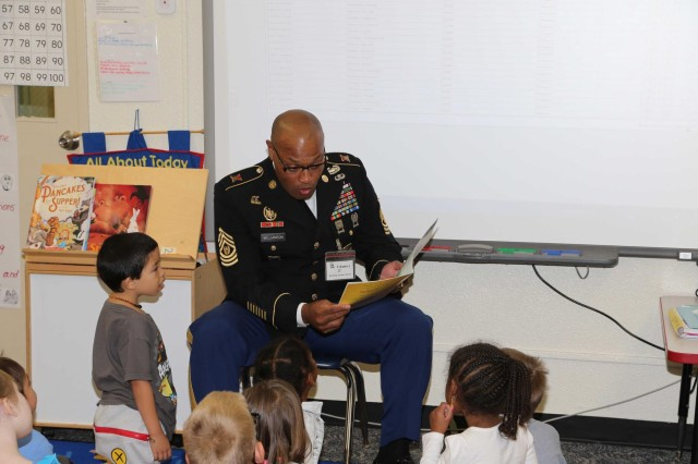"Command Sgt. Maj. Shelton R. Williamson, (left) command sergeant major for the 10th Regional Support Group, reads ""The Amazing Turkey Rescue"" to kindergarten students at Bob Hope Primary School on Kadena Air Base, Okinawa, Japan in support of American Education Week, Nov 20. The 10th RSG adopted Bob Hope Primary School as their partnership school and is planning to visit the school quarterly to assist with various projects as well as read and have fun with the students."