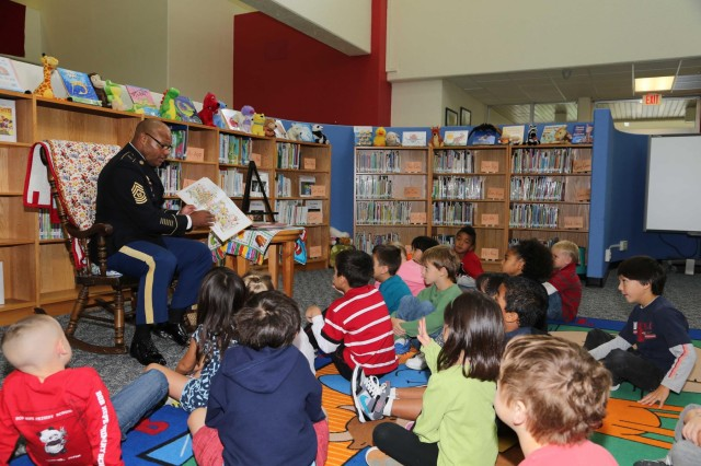 "Command Sgt. Maj. Shelton R. Williamson, (left) command sergeant major for the 10th Regional Support Group, reads ""Thanksgiving Is Here"" to a first grade class at Bob Hope Primary School on Kadena Air Base, Okinawa, Japan in support of American Education Week, Nov. 20. The 10th RSG adopted Bob Hope Primary School as their partnership school and is planning to visit the school quarterly to assist with various projects as well as read and have fun with the students."