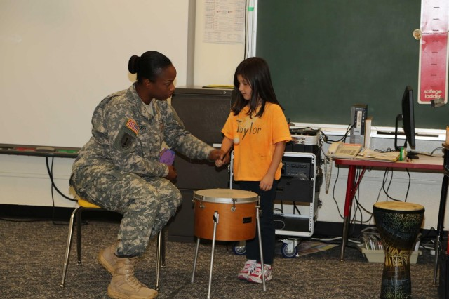 Sgt. Jamara Ross, (Left) 10th Regional Support Group, Support Operations and Maintenance works with a kindergarten student during a music lesson, Nov. 20, at Bob Hope Primary School, Kadena Air Base, Okinawa, Japan. Soldiers assigned to the 10th RSG agreed to adopt Bob Hope Primary School planning to visit the school quarterly to assist with various projects as well as read and have fun with the students.