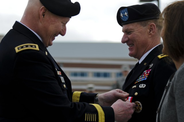 From left, U.S. Army Gen. Robert W. Cone, Training and Doctrine Command commanding general, presents the Army Distinguished Service Medal to Maj. Gen. Bradley W. May, former Initial Military Training deputy commanding general, during a change of responsibility ceremony and retirement review at Fort Eustis, Va., Nov. 22, 2013. May entered the Army as an armored cavalry officer, and has served as a commander, executive officer and deputy commander under various armored cavalry units during his 33-year long career.