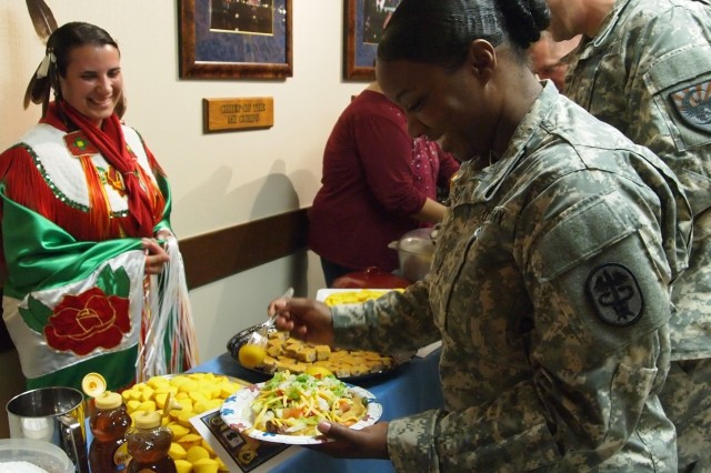 Sgt. Kalie Jones, left, Headquarters and Headquarters Company, U.S. Army Intelligence Center of Excellence, wears a traditional Cherokee/Lumbee outfit as she serves Native American food at the Native American Heritage Month celebration Friday. Attendees such as Sgt. 1st Class Tia Chamblee, senior dental noncommissioned officer, Runion Dental Clinic, Fort Huachuca Dental Activity, had the opportunity to sample fry bread with chili beans, and different breads made from squash, beans and corn pone.