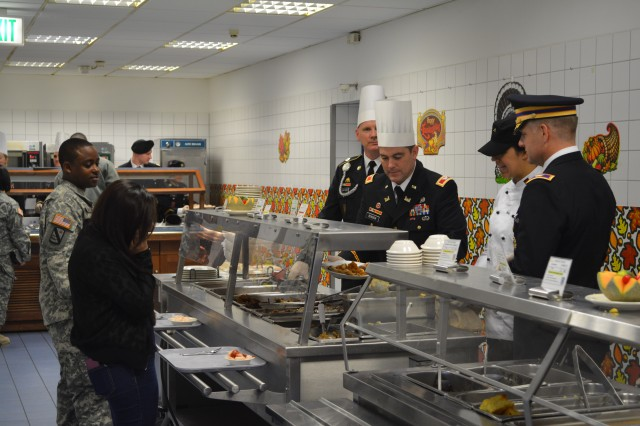Col. Christopher M. Benson, behind the counter second from left, U.S. Army Garrison Ansbach commander, and Command Sgt. Maj. William E. Funcheon, behind the counter left, USAG Ansbach command sergeant major, serve Soldiers, Family members and members of the USAG Ansbach community food for Thanksgiving Nov. 27, 2013, at the Katterbach Dining Facility.