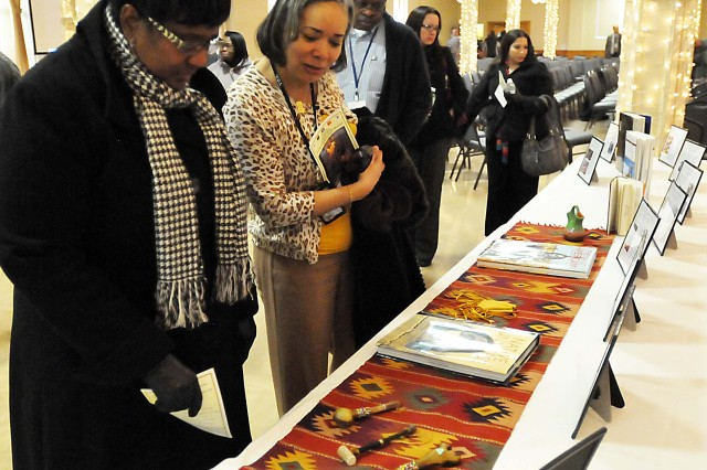 """National American Indian Heritage Month"" observance attendees look at American Indian literature and products displayed at the event Nov. 26 in Rock Island Arsenal's Heritage Hall. (Photo by Jon Micheal Connor, ASC Public Affairs)"