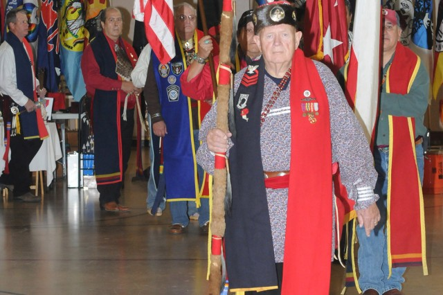 Retired Navy Chief Bill Bellinghausen leads the procession for the Grand Entry around the drum circle, Nov. 16, 2013, at the Fort Sam Houston (Texas) Native American Indian Heritage Month Pow Wow in the Fort Sam Houston Teen and Youth Center. The grand entry honors the National and service colors as well as the flag and participating dignitaries.