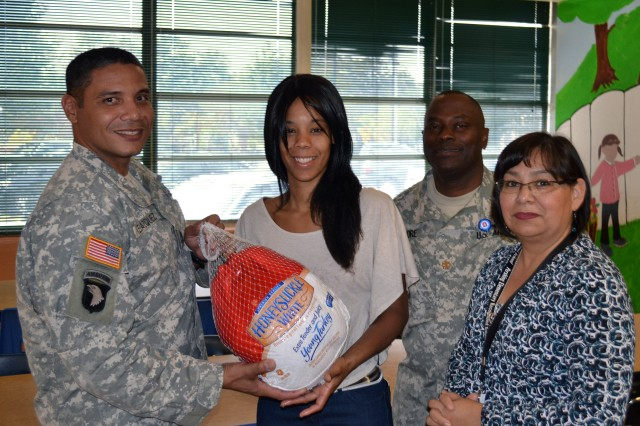 SAN ANTONIO - Sgt. 1st Class Julio Velazquez (far left), hands a turkey to Kristal Bethel, a local mother, as Maj. Barrick Elmore and Angelica Castillo (right) watch on during the Pershing Elementary School Turkey give-away Nov. 20 at Pershing Elementary. The turkeys were donated by the Soldiers and civilians of U.S. Army North (Fifth Army) and delivered by Soldiers with Headquarters, Headquarters Battalion, Army North. Velazquez is the battalion's logistics noncommissioned officer-in-charge, and Elmore is the battalion's logistics officer-in-charge. Castillo is the Pershing Elementary parent and family liaison.