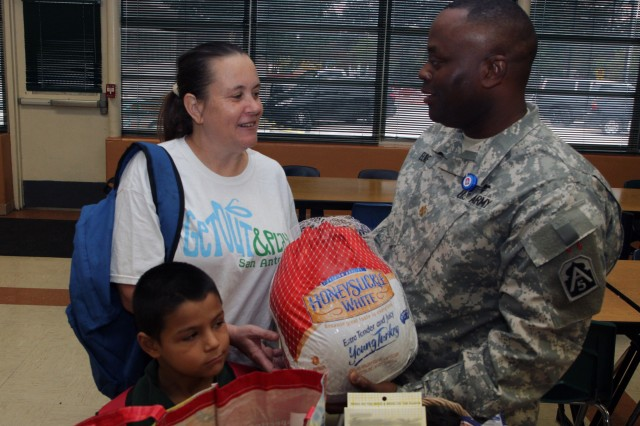 SAN ANTONIO - Maj. Barrick Elmore presents a Thanksgiving turkey to Louise Rivera, a local parent, and her grandson, Juan Rivera, a first-grade student at Pershing Elementary School, during the Pershing Elementary turkey give-away Nov. 20 at Pershing Elementary. Headquarters, Headquarters Battalion, U.S. Army North (Fifth Army), is partnered with Pershing Elementary through the Fort Sam Houston Adopt-A-School program. Elmore is the battalion's logistics officer-in-charge.
