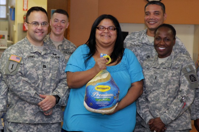 SAN ANTONIO - Leaders from Headquarters, Headquarters Battalion, U.S. Army North (Fifth Army) meet with Viola Mauricio (center), a local mother, during the Pershing Elementary School turkey give-away Nov. 20 at Pershing Elementary. Army North is partnered with Pershing Elementary through the Fort Sam Houston Adopt-A-School program.
