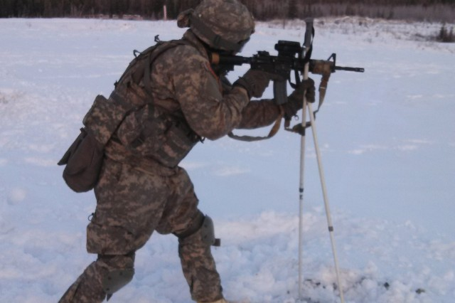 Private First Class Paul Longale of 3rd Platoon, Bravo Company, 1-24 Infantry  Battalion, a native of Tucson, Az., demonstrates an arctic firing position  using ski poles as a bipod while on Manchu Range.