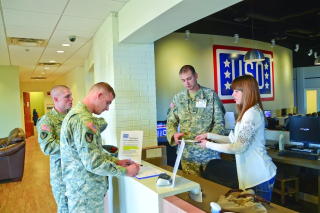 Specialist Damon Kress and Pvt. Brian Wook, Soldiers from 591st Engineering Company, 326th Engineering Battalion, 101st Sustainment Brigade, 101st Airborne Division, are greeted at the Fort Campbell USO front desk by Sgt. Grant Feeny, a Soldier assigned to the Warrior Transition Battalion, and his wife Leslie, Nov. 12. The Feenys began volunteering at the USO as part of a WTB worksite program.