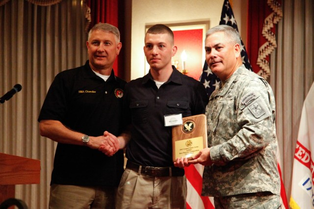 Vice Chief of Staff of the Army Gen. John F. Campbell and Sgt. Maj. of the Army Ray Chandler present Spc. Michael Sands with the third-place plaque earned during the 2013 Army Best Warrior Competition at Fort Lee, Va., Nov. 22, 2013. (U.S. Army photo by Sgt. Stephen J. Schmitz/Released)