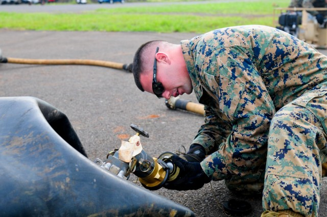 Marine Cpl. John Fazio, bulk fuel specialist, Marine Wing Support Detachment 24, hooks up a fuel hose to a 500-gallon fuel blivet to set up a forward area refueling system during the 25th Combat Aviation Brigade, 25th Infantry Division, first joint service Forward Arming and Refueling Point Rodeo competition on Wheeler Army Airfield, Hawaii, Nov. 20.