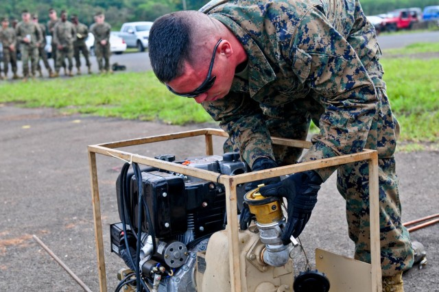 Marine Sgt. Robert Sarvak, bulk fuel specialist, Marine Wing Support Detachment 24, preps a motor with the correct hose connectors to set up a forward area refueling system during the 25th Combat Aviation Brigade, 25th Infantry Division, first joint service Forward Arming and Refueling Point Rodeo competition on Wheeler Army Airfield, Hawaii, Nov. 20.