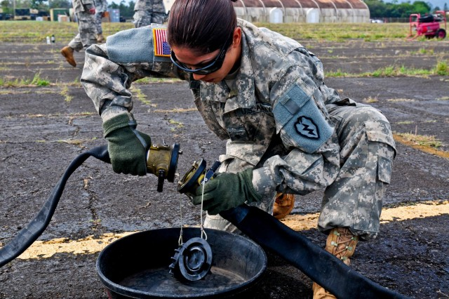 "Spc. Karina Anaya, petroleum supply specialist, Troop E, 2nd Squadron, 6th Cavalry Regiment, 25th Combat Aviation Brigade, 25th Infantry Division, connects fuel hoses on an Extended Range Fuel System, also known as the ""Fat Cow,"" during the 25th Combat Aviation Brigade, 25th Infantry Division, first joint service Forward Arming and Refueling Point Rodeo competition on Wheeler Army Airfield, Hawaii, Nov. 20."
